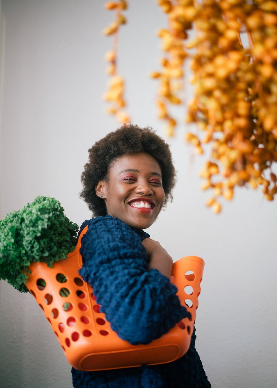happy young black woman holding basket with lettuce on shoulder and cluster of yellow dates in grocery store on gray background